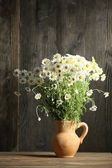 Beautiful bouquet of daisies in pitcher on wooden background — Stock Photo