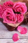 Beautiful pink roses in suitcase, closeup — Stock Photo