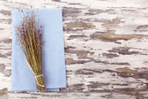 Beautiful dry flowers on napkin on wooden background — Stock Photo