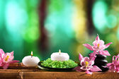 Beautiful spa composition with flowers and candles on bright background — Stok fotoğraf