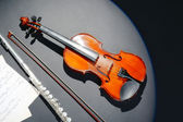 Violin and flute with music notes on dark background — 图库照片