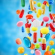 Falling colorful medical pills on blue background — Photo #76528629