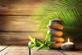 Spa stones, candle on wooden background — Stock Photo