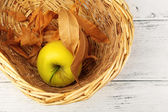 Apple with dried leaves in wicker basket on wooden background — Stock Photo