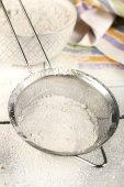Sifting flour through sieve — Stock Photo