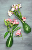 Beautiful alstroemeria in vases on wooden background — Stock Photo