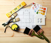 Construction instruments, plan and brushes on wooden table background — Stock Photo