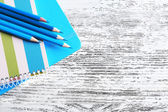 Turquoise crayons and diary on wooden table, closeup — Stock Photo