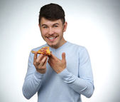 Young man eating piece of pizza on gray background — Stock Photo