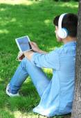 Man with headphones resting under tree in park — Stock Photo