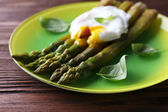Roasted asparagus with poached egg on plate on table close up — Stock Photo