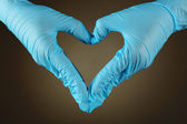 Doctor's hands making heart shape on gray background — Stock Photo
