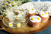 Cup of chamomile tea with chamomile flowers and tasty muffins on tray, on color wooden background — Stock Photo