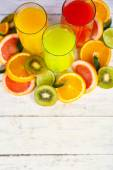 Glasses of different juice with fruits and mint on wooden background — Stock Photo