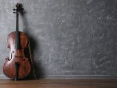 Classical cello and bow on gray wall background — Stock Photo