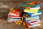 Stos książek i artykułów piśmiennych na drewniane tła — Zdjęcie stockowe
