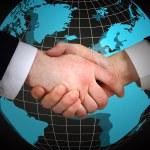 Business handshake on world map background — Stock Photo #76742309
