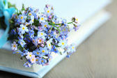 Forget-me-nots flowers on book, on wooden background — Stock Photo