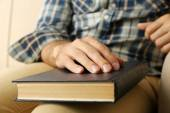 Young man with book on sofa close up — Stock Photo