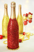 Decorative champagne bottles with beads and Christmas balls on light background — Stock Photo