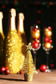 Decorative champagne bottles with Christmas balls on dark background — Stock Photo