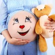 Beautiful young pregnant with baby toy  and picture on her belly, on light background — Stock Photo #77030191