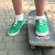 Young skateboarder in gumshoes standing on skate — Stock Photo #77032305