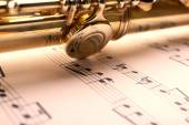Silver flute on music notes background — Stock Photo
