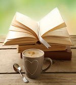 Cup of coffee and books on wooden table, on green background — Stock Photo