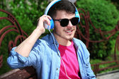 Man with headphones resting on bench in park — Stock Photo