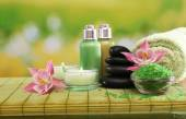 Spa still life with flowers and candlelight on green blurred background — Stock Photo