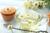 Cup of chamomile tea with chamomile flowers and tasty muffins on color wooden background — Stock Photo