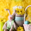 Easter bunny with painted Easter eggs with flowers on wooden table on yellow  background — Stock Photo #77206005