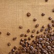 Frame of coffee beans on color sackcloth background — Stock Photo #77240866
