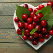 Sweet cherries with green leaves on plate, on wooden background — Stock Photo #77248614