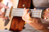 Young man playing on acoustic guitar close up — Stock Photo