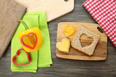 Bread slice with cut in shape of heart and pepper on table close up — Stock Photo