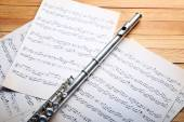 Silver flute with music notes on wooden table close up — Stock Photo