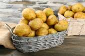 Young potatoes in wicker baskets on wooden table close up — Stock Photo