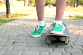 Young skateboarder in gumshoes standing on skate — Stock Photo