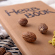 Dried herb with nutmegs and book — Stock Photo #77450530