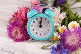 Alarm clock with wild flowers — Stock Photo