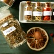 Assortment of spices in glass bottles on wooden background — Stock Photo #77577324