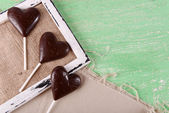 Chocolate heart shaped candies on sticks on sackcloth, closeup — Stock Photo