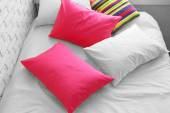 Lit confortable avec des coussins colorés dans la chambre — Photo