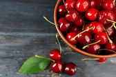 Fresh cherries in bowl on wooden background — Stock Photo