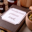 Medicinal plants book with dried herbs and bottles on table close up — Stock Photo #77705310