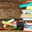 Stack of books and stationery on wooden background — Stock Photo #77706798