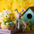 Easter bunny with painted Easter eggs with flowers on wooden table on yellow  background — Stock Photo #77709612
