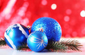 Beautiful Christmas balls on red blurred background — Stock Photo